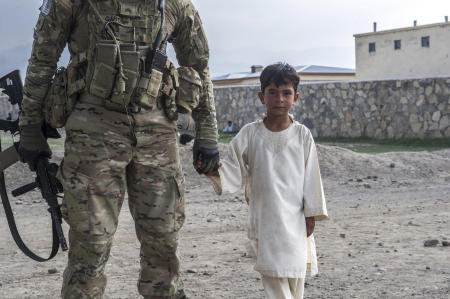 Tani District, Khost Province, Afghanistan- A US Army sergeant assigned to the 1st Infantry Division holds the hand of Ramn Akbal Khan, a student at the local elementary school. With the help of an interpreter and a member of the Afghan National Amy, the student and the sergeant shared culture-based education, with the student teaching the sergeant about local customs, and the sergeant teaching the student about security in the region. 