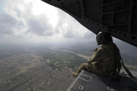 With combat resupply missions running daily, and troops being moved around the country, I often found myself aboard the most common mode of travel, a helicopter. Seated on the back of a Chinook helicopter ramp, a member of the helicopters crew keeps a watchful eye for any threats that might arise. Threats to the aircraft can be from enemy fire or from obstacles the pilots cannot see. These crewmembers also handle making sure that passengers approach the aircraft in a safe manner.