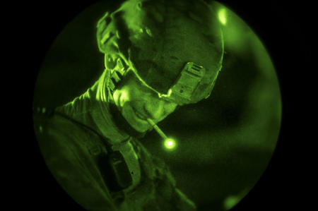 During a nighttime mission, a US Army solder takes a moment to smoke a cigarette.
