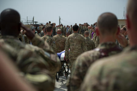 As the detail passed down the ranks, the soldiers individually saluted their fallen comrade. The pace was slow, and reverent. A UH-60 Blackhawk helicopter from the 10th Mountain Division sat on the helipad. The detail approached the Blackhawks rear door. The crew chiefs saluted, and held their salute as the wheels of the stretcher were removed. The detail preformed a 180 degree turn, placing the head of the fallen solder into the Blackhawk first. The Chaplain asked the assembly to kneel in prayer. The soldiers took a knee. With eyes closed, the Chaplain placed his hand on the flag, and held his right hand out as he prayed.