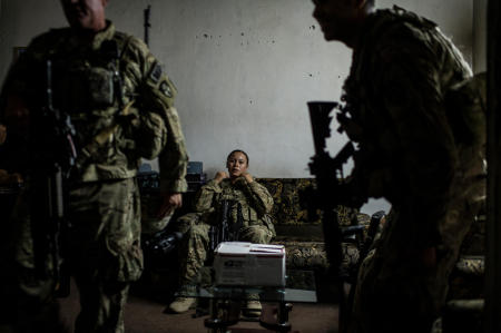 During a nighttime mission, a US Army Sergeant assigned to the 49th Military Police Brigade takes one last moment of rest before setting out back to the base. This mission consisted of meeting with the local Afghan National Police Chief about increased risks in his area, and what the ISAF can do about it. The box on the table contained police notebooks, radios, and other essential items that the US Armys Military Police were providing to the Police Chief.