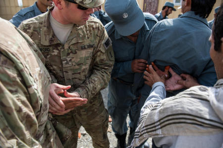 Soldiers from the U.S. Armys 1st Infantry Division, with aid of an interpreter, demonstrate methods for controlling a suspect to officers of the Afghan National Police.